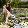Happy young female with Garden streamlet relaxing near the pond. — Stock Photo #3501426