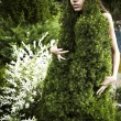 The girl in a dress from a decorative fur-tree. - Stock Photo