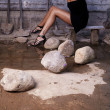 Sexual girl in black dress inside stone quarry among old shovels - Stock Photo