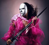 Woman warrior in a silver mask with a sword in hands. — Stock Photo