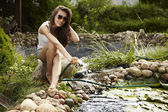 Happy young female with Garden streamlet relaxing near the pond. — Stock Photo