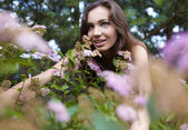 Beautiful girl sitting among the bush flowers — Stok fotoğraf