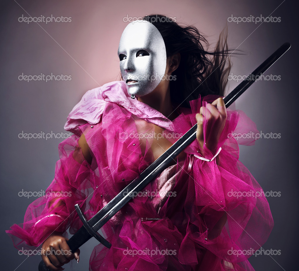Woman warrior in a silver mask with a sword in hands. Photo.  Stock Photo #3501284