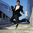 Jumping businessman over urban background - Stock Photo