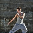 Young attractive man dancing in urban background - ストック写真