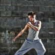 Young attractive man dancing in urban background — Stock Photo
