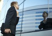 Hombre de negocios vano comprobando su mira en el espejo — Foto de Stock