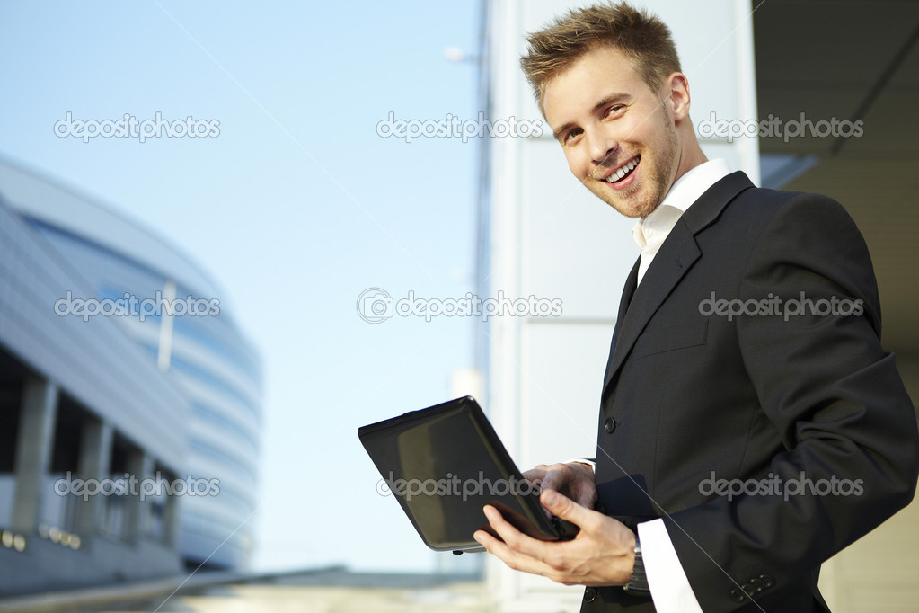 Closeup portrait of a happy young businessman using laptop on street — Stock Photo #3551717
