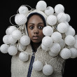 Portrait of African woman covered with fixtures in form of ball for a golf — Stock Photo
