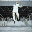 Jumping businessman over urban background — Stock Photo #3882431