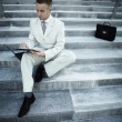 Handsome male business executive sitting on stairs outside a building with — Stock Photo #3882483