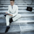 Royalty-Free Stock Photo: Handsome male business executive sitting on stairs outside a building with