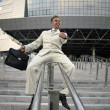 Young businessman with briefcase running on stair - Photo