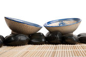 Two cups and stones on mat — Stock Photo