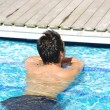Young man relaxing at the edge of the swimming pool - Stock Photo