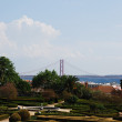 Enchanted Ajuda garden with April 25th bridge in Lisbon, Portugal — Stock Photo #3904860