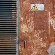 High voltage sign on a rusty door — Stock Photo