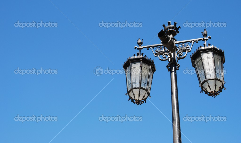 Vintage lamp posts against blue sky background  Stock Photo #3906932