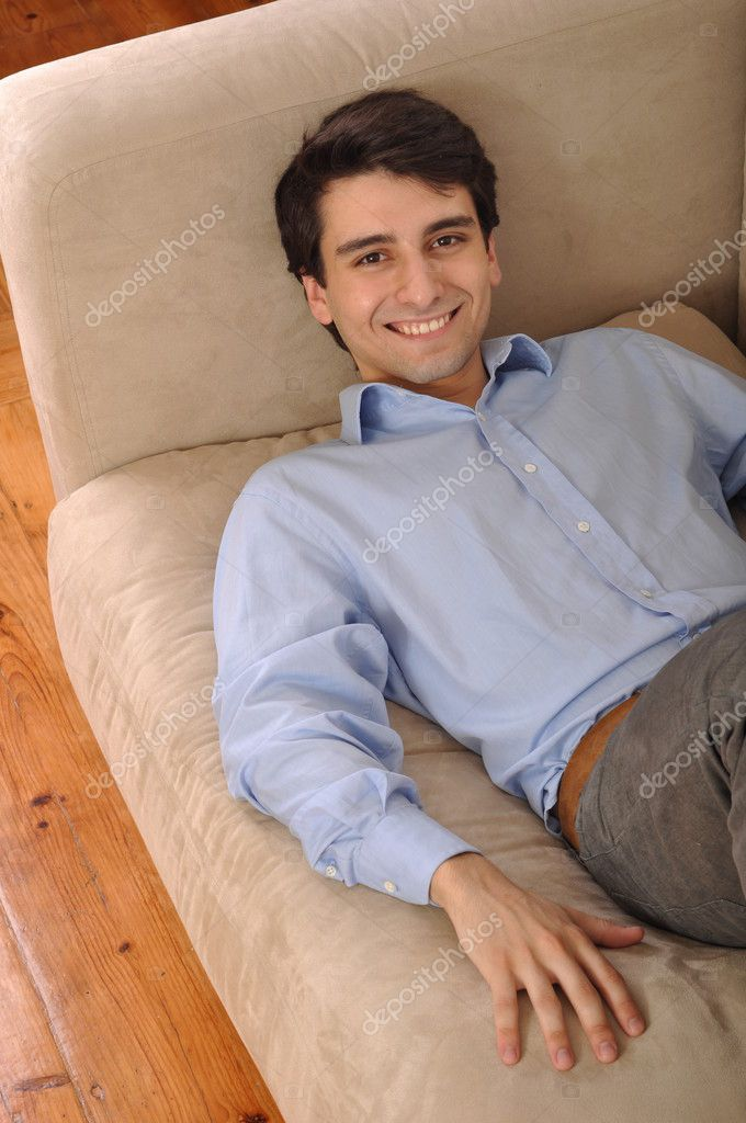 Attractive young man lying and relaxing on the couch — Stock Photo #3907264