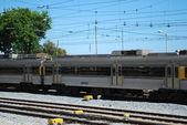 šedé vlak kolem místní vesnice — Stock fotografie