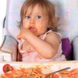 Messy baby girl eating spaghetti — Stock Photo