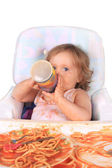 Messy baby girl drinking juice and eating spaghetti — Stock Photo
