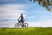 Man on a bike in a field — Stock Photo