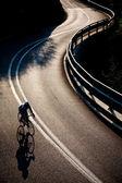 Cyclist riding along a mountain road — Stock Photo