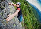 Young white man climbing a steep wall — Stock Photo