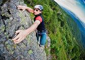 Young white man climbing a steep wall — Stock Photo