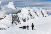 Mountaneers walking on a glacier — Stock Photo
