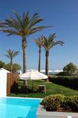 Swimming pool, sunbeds and palms at luxury villa, Crete, Greece — Stock Photo