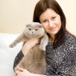 The girl holds a grey cat on hands — Stock Photo #3215828