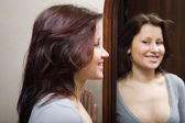 The girl looking at itself in a mirror — Stock Photo