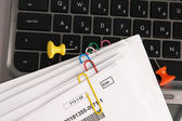 Paper documents with clips on laptop keyboard — Stock Photo