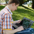 Young man using laptop in summer park — Stock Photo