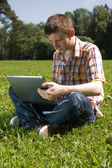 Man using laptop in summer park — Stock Photo
