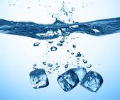 Ijsblokjes gedaald in water met splash — Stockfoto