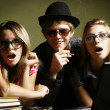 Stock Photo: Fashion young guys and girls sitting together and having fun . Art photo