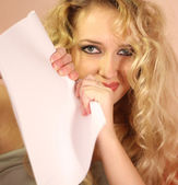 Blond girl tear white clean sheet o — Stock Photo