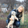 Girl played with a small white dog — Stock Photo