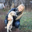 Blond girl played with a small white dog — Stock Photo