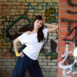 Young girl near the walls with graffiti — Stock Photo