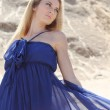 Girl in dark blue dress on the sand — Stock Photo #3461373