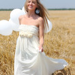 Smiling girl with white balloons - Stock Photo