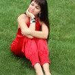 Brunette girl in red on the grass — Stock Photo