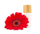 Cream bottle with a red gerberas — Stock Photo