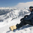 Young snowboarder sitting - Stock Photo