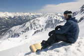 Young snowboarder sitting — Stock Photo