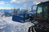 Snowcat in mountains in the evening — Stockfoto
